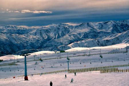 Una vista espectacular de los esquiadores y hermosas montañas al atardecer en Valle Nevado Foto de archivo - 33254320