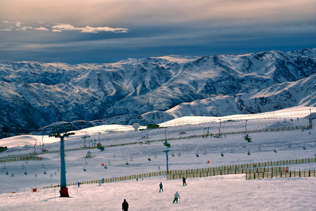 Breathtaking view of skiers and beautiful mountains at sunset in Valle Nevado