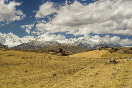 passing over: Clouds passing over sunlit meadows of Cordillera Negra in Peru Stock Photo