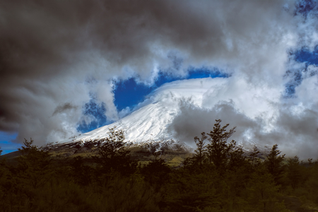 perez: Breathtaking view of grey clouds rolling over mountain peak in Parque Nacional Vicente Perez Rosales
