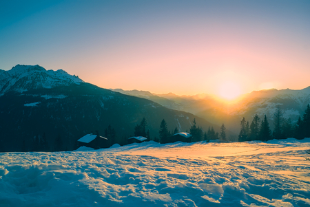 Picturesque view of sunset over snow-covered mountains in photo