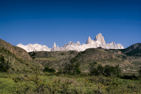 los glaciares: Panoramic view of snowy mountains rising above grassy hills in Los Glaciares National Park