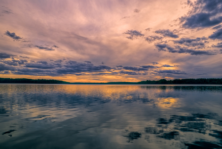 windswept: Breathtaking view of sunset behind windswept sky reflected in a lake