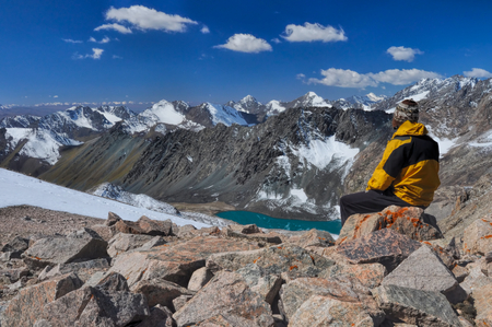 Young hiker on mountain summit in scenic Tian Shan range in Kyrgyzstan, Ala Archa national park Standard-Bild