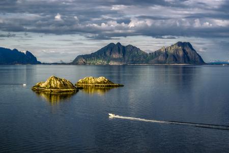 speedboat: Picturesque view of Lofoten islands with speedboat on the ocean Stock Photo