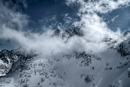 passing over: Panoramic view of clouds passing over snowy mountains Stock Photo