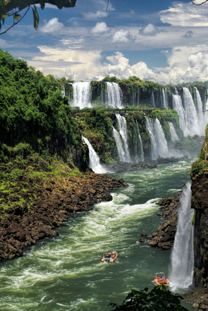 Dramatic view of Iguazu waterfalls in Argentina with tourist boats on the river