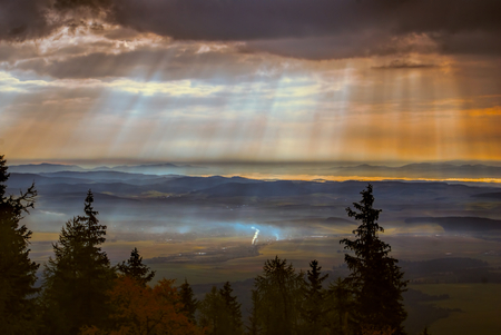 godly: Godly light rays passing through clouds in the early morning above hilly countryside