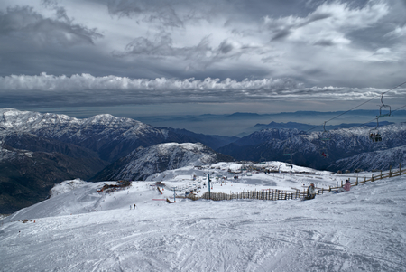 piste: Picturesque view of piste in Valle Nevado under gloomy grey sky Stock Photo