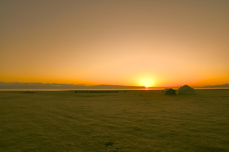 nomadic: Scenic sunrise over traditional yurt of nomadic tribe on green grasslands in Kyrgyzstan Stock Photo