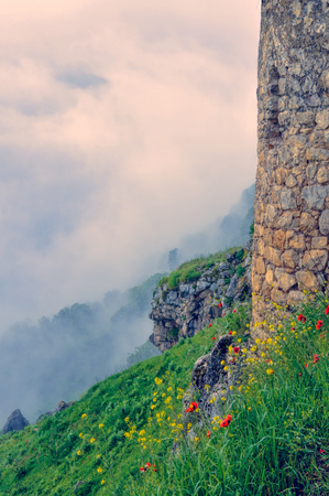 Tower stone wall above mist on green landscape of mountainous Karabakh photo