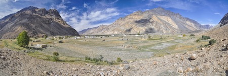 grain fields: Scenic panorama of small remote village with grain fields in Tajikistan on sunny day Stock Photo
