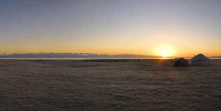 lake dwelling: Scenic panorama of sunset on green grasslands in Kyrgyzstan with traditional namodic yurt