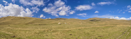 nomadic: Scenic panorama of green grasslands in Kyrgyzstan with traditional nomadic yurt Stock Photo