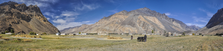 grain fields: Scenic panorama of remote village with grain fields in Tajikistan on sunny day Stock Photo