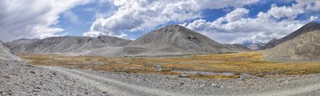 Panorama panoramica della strada sterrata che porta attraverso il paesaggio arido in Tagikistan Archivio Fotografico