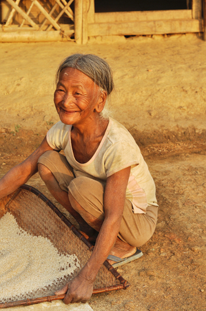 sift: Nagaland, India - March 2012: Happy old woman sifts flour in Nagaland, remote region of India. Documentary editorial. Editorial