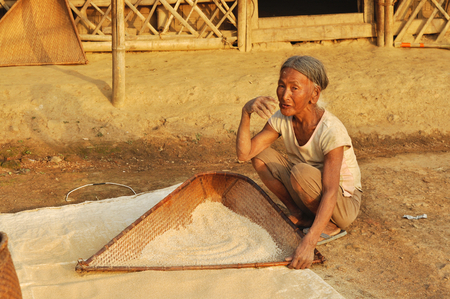 sift: Nagaland, India - March 2012: Old woman sifts flour in Nagaland, remote region of India. Documentary editorial.
