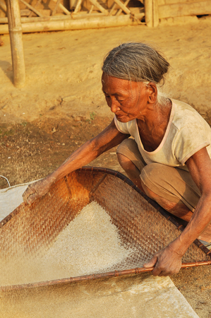 nagaland: Nagaland, India - March 2012: Old woman sifts flour in Nagaland, remote region of India. Documentary editorial.