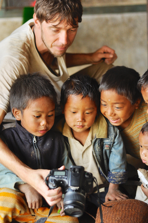 Nagaland, India - March 2012: Young photographer shows pictures on digital camera to small boys in village in Nagaland, remote region of India. Documentary editorial. Editorial