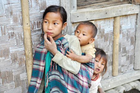 Nagaland, India - March 2012: Small girl with younger brother and sister in Nagaland, remote region of India. Documentary editorial. Editorial