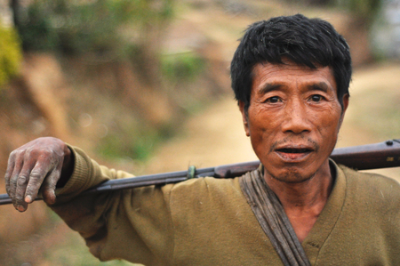 Nagaland, India - March 2012: Portrait of young man with rifle in Nagaland, remote region of India. Documentary editorial.