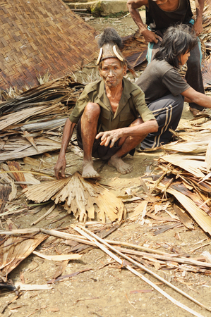 Nagaland, India - March 2012: Young man works with dried leafs in Nagaland, remote region of India. Documentary editorial.