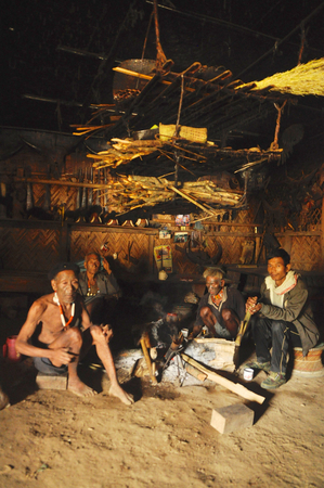 sit around: Nagaland, India - March 2012: Men sit around fire  in Nagaland, remote region of India. Documentary editorial.