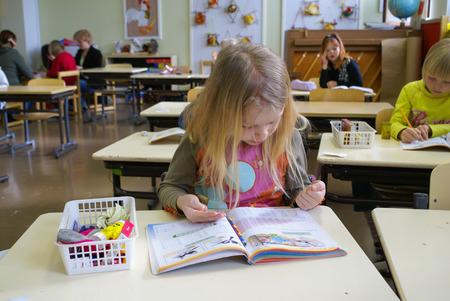Finlandia - mayo de 2007: Los números de Cuentas jovenes de la muchacha con la ayuda de sus manos durante la lección de las matemáticas en la escuela primaria en Finlandia. editorial documental Foto de archivo - 54316447