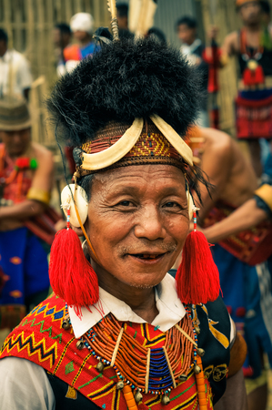 Mon, Nagaland - April 2012: Older native man in traditional colourful costume and large hat made of fur smiles to photocamera at Aoleang festival in Mon, Nagaland. This festival showcases rich cultural heritage of this country. Documentary editorial.