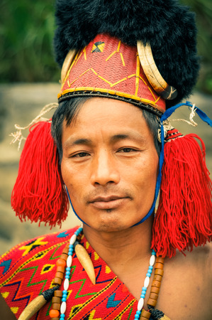 Mon, Nagaland - April 2012: Photo of a man with traditional hat with fur posing to photocamera at Aoleang festival in Mon, Nagaland. At this festival people can see indigenous dances and games. Documentary editorial.