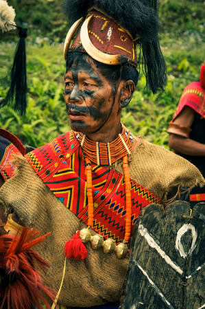 Mon, Nagaland - April 2012: Photo of man in traditional costume with large hat with black colour on his face looking left at Aoleang festival in Mon, Nagaland. This festival showcases rich cultural heritage of this country. Documentary editorial.