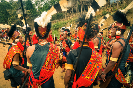 documentary: Mon, Nagaland - April 2012: Native men in traditional costumes and large hats stand in circle and dance at Aoleang festival in Mon, Nagaland. Documentary editorial. Editorial