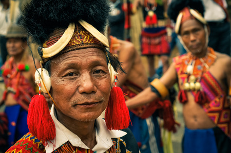 Mon, Nagaland - April 2012: Older native man in traditional colourful costume and large hat made of fur looks to photocamera at Aoleang festival in Mon, Nagaland. Documentary editorial.