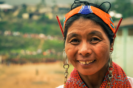 Mon, Nagaland - April 2012: Native woman with traditional necklace and with traditional orange headband made of beads wears earrings and smiles to photocamera at Aoleang festival in Mon, Nagaland. Documentary editorial.