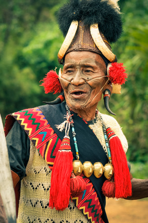 nagaland: Mon, Nagaland - April 2012: Photo of old talking man in traditional costume with hat and large plugs in ears at Aoleang festival in Mon, Nagaland. At this festival people can see indigenous dances and games. Documentary editorial.