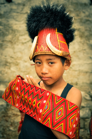 documentary: Mon, Nagaland - April 2012: Young boy with typical hat with fur and bones holds traditional colourful belt and looks to photocamera at Aoleang festival in Mon, Nagaland. Documentary editorial. Editorial