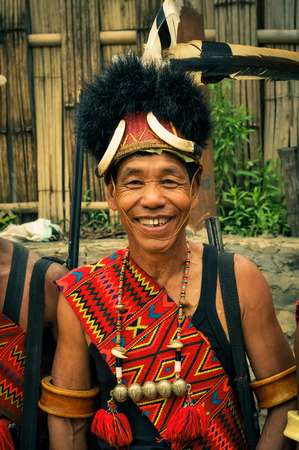 nagaland: Mon, Nagaland - April 2012: Smiling man in costume and hat made of fur poses to photocamera at Aoleang festival in Mon, Nagaland. This festival showcases rich cultural heritage of this country. Documentary editorial. Editorial
