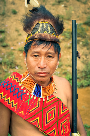 nagaland: Mon, Nagaland - April 2012: Native man in costume with large hat made of fur holds his rifle and looks to photocamera at Aoleang festival in Mon, Nagaland. Aoleang is main festival of Konyaks from northern Nagaland. Documentary editorial. Editorial