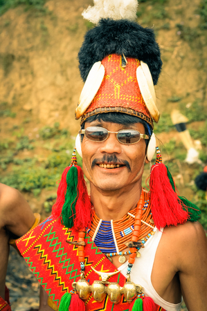 nagaland: Mon, Nagaland - April 2012: Native man in complex traditional costume with large hat made of fur wears glasses and smiles to photocamera at Aoleang festival in Mon, Nagaland. Aoleang is main festival of Konyaks from northern Nagaland. Documentary editoria