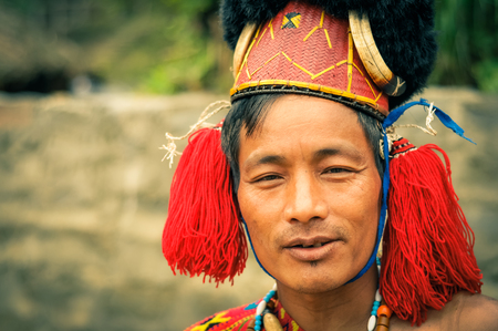 documentary: Mon, Nagaland - April 2012: Photo of man with traditional hat with fur posing to photocamera at Aoleang festival in Mon, Nagaland. Documentary editorial. Editorial