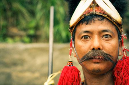 Mon, Nagaland - April 2012: Native man with traditional hat and long moustache looks with wide-open eyes to photocamera at Aoleang festival in Mon, Nagaland. Documentary editorial.