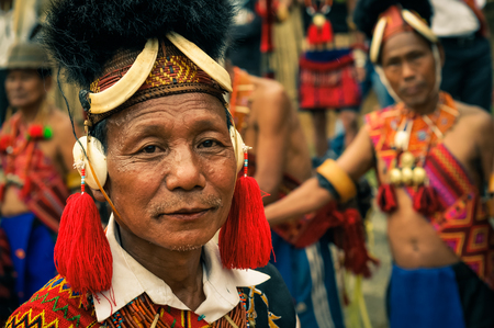 Mon, Nagaland - April 2012: Native man in traditional colourful costume and large hat made of fur looks to photocamera at Aoleang festival in Mon, Nagaland. Aoleang is main festival of Konyaks from northern Nagaland. Documentary editorial. Editorial