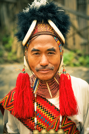 documentary: Mon, Nagaland - April 2012: Man in traditional costume and hat with nice face and grey moustache looks  to photocamera at Aoleang festival in Mon, Nagaland. Documentary editorial.