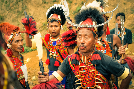 documentary: Mon, Nagaland - April 2012: People in traditional costumes and large hats dance at Aoleang festival in Mon, Nagaland. Documentary editorial.
