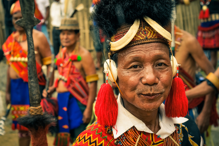 documentary: Mon, Nagaland - April 2012: Handsome native man in traditional costume with large hat made of fur smiles to photocamera at Aoleang festival in Mon, Nagaland. Aoleang is main festival of Konyaks from northern Nagaland. Documentary editorial.