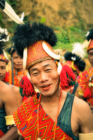 documentary: Mon, Nagaland - April 2012: Man in traditional costume and large hat smiles to photocamera at Aoleang festival in Mon, Nagaland. At this festival people can see indigenous dances and games and hear traditional songs. Documentary editorial.