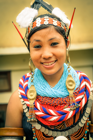 Mon, Nagaland - April 2012: Beautiful young girl in traditional costume with long golden earrings and headband smiles to photocamera at Aoleang festival in Mon, Nagaland. This festival showcases rich cultural heritage of this country. Documentary editoria