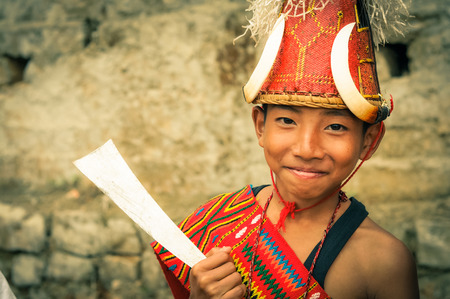 Mon, Nagaland - April 2012: Photo of smiling young boy with typical large hat with bones in traditional costume at Aoleang festival in Mon, Nagaland. Documentary editorial.