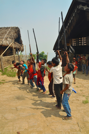 Aoleang, Nagaland, India - April 2012:  Native boys with guns dancing and singing on the street during Aoleang festival in Aoleang, Nagaland, India. Documentary editorial.